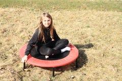 Blondes Mädchen, das auf Trampoline sitzt Lizenzfreies Stockfoto