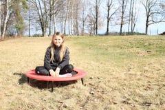 Blondes Mädchen, das auf Trampoline sitzt Stockfotografie