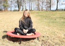 Blondes Mädchen, das auf Trampoline sitzt Stockfoto