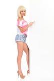 Blondes Mädchen, das auf weiße große Fahne zeigt Stockfotografie