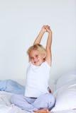 Blondes Mädchen, das in Bett ausdehnt Lizenzfreie Stockbilder