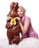 Blondes Mädchen, das Bowtie einer Schokolade Ostern justiert  Stockfoto