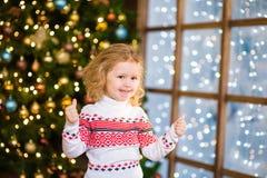 Blondes Mädchen, das Daumen oben auf dem Hintergrund von Weihnachten-tre zeigt Lizenzfreies Stockbild