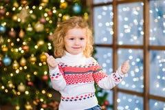 Blondes Mädchen, das Daumen oben auf dem Hintergrund von Weihnachten-tre zeigt Lizenzfreie Stockfotos