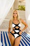 Blondes Mädchen, das in den einteiligen Schwarzweiss-Badeanzügen steht Lizenzfreie Stockbilder