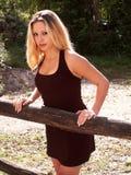 Blondes Mädchen, das den Zaun bereitsteht stockfotografie