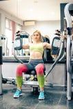 Blondes Mädchen, das an der Turnhalle trainiert Lizenzfreie Stockfotografie