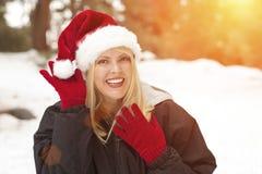 Blondes Mädchen, das draußen Santa Hat und Handschuhe im Schnee trägt Lizenzfreie Stockbilder