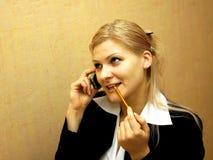 Blondes Mädchen, das durch Handy spricht Stockbilder