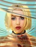 Blondes Mädchen, das durch Jalousie schaut stockfoto