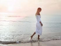 Blondes Mädchen, das durch das Meer im Sonnenuntergang geht lizenzfreies stockbild