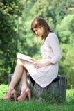 Blondes Mädchen, das ein Buch im Park liest Stockfoto