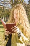 Blondes Mädchen, das ein Buch im Park liest Stockbild