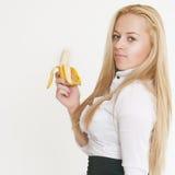 Blondes Mädchen, das eine Banane genießt Stockbild