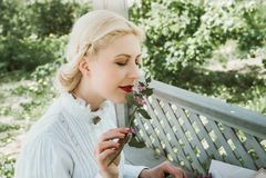 Blondes Mädchen, das eine Blume riecht lizenzfreie stockfotos