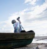Blondes Mädchen, das in einem alten Boot, eingewickelt in einer Decke und gefilmt dem Himmel sitzt Lizenzfreie Stockbilder