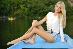 Blondes Mädchen, das in einem Boot in einem See sitzt Stockfoto