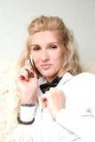 Blondes Mädchen, das an einem Telefon spricht Lizenzfreies Stockbild