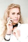 Blondes Mädchen, das an einem Telefon spricht Stockbild