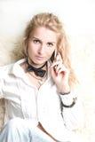 Blondes Mädchen, das an einem Telefon spricht Stockfotos