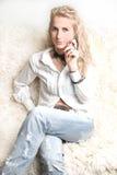 Blondes Mädchen, das an einem Telefon spricht Stockfotografie