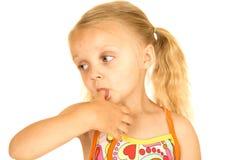 Blondes Mädchen, das einen Badeanzug mit ihrem Daumen in ihrem Mund trägt Lizenzfreie Stockfotos