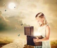 Blondes Mädchen, das einen Schatz-Kasten öffnet lizenzfreie stockfotografie
