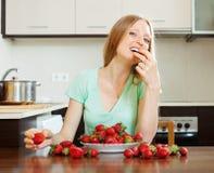 Blondes Mädchen, das Erdbeere isst Stockfoto