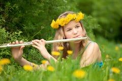 Blondes Mädchen, das Flöte im Park spielt Stockfoto