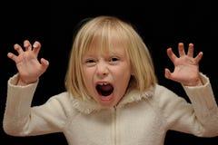 Blondes Mädchen, das furchtsames Gesicht bildet Stockfoto