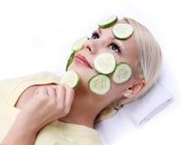 Blondes Mädchen, das Gurkeschablone auf ihrem Gesicht anwendet Lizenzfreie Stockfotografie