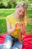 Blondes Mädchen, das Handy und hörende Musik mit headphon hält Lizenzfreie Stockfotos