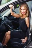 Blondes Mädchen, das hinter dem Rad sitzt und Autoschlüssel hält Lizenzfreie Stockbilder