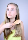 Blondes Mädchen, das ihr Haar kämmt Lizenzfreies Stockbild