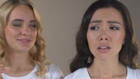 Blondes Mädchen, das ihre zarte Haut lacht mit Freund mit Akne auf Gesicht genießt stock footage