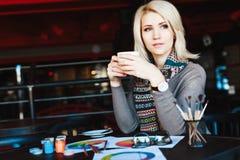 Blondes Mädchen, das im Café mit Tasse Tee sitzt Stockbilder