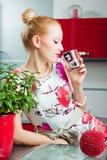 Blondes Mädchen, das im Innenraum der Küche trinkt Lizenzfreies Stockbild