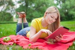 Blondes Mädchen, das im Park mit Tablette auf der roten Bettdecke liegt lizenzfreie stockfotos