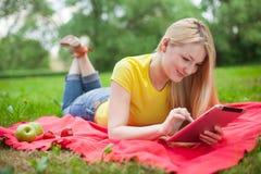 Blondes Mädchen, das im Park mit Tablette liegt Lizenzfreie Stockfotografie