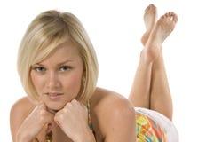 Blondes Mädchen, das im Sommerkleid niederlegt lizenzfreies stockbild