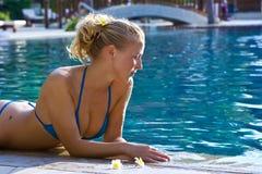 Blondes Mädchen, das im Wasser im Pool sich entspannt Lizenzfreie Stockbilder