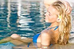 Blondes Mädchen, das im Wasser im Pool sich entspannt Lizenzfreies Stockfoto