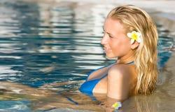 Blondes Mädchen, das im Wasser im Pool sich entspannt Lizenzfreie Stockfotografie