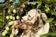 Blondes Mädchen, das ja eine Pflaume von einer Baumhüttensonnen-Sommernatur isst Lizenzfreies Stockfoto