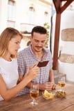 Blondes Mädchen, das Kerl etwas auf Mobiltelefon zeigt Stockbild