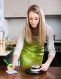 Blondes Mädchen, das Kuchen auf Küchenskalen wiegt Stockfoto