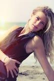Blondes Mädchen, das in Meer aufwirft Schwarzes Kleid Stockfoto