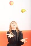 Blondes Mädchen, das mit Apfel und Birne jongliert Lizenzfreie Stockbilder