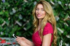 Blondes Mädchen, das mit dem intelligenten Telefon spielt Lizenzfreies Stockbild