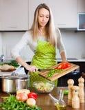 Blondes Mädchen, das mit Gemüse kocht Lizenzfreies Stockbild